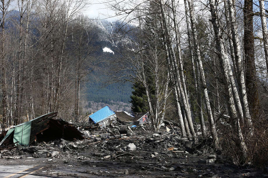 A demolished house sits in the mud on Highway 530, Sunday, March 23, 2014 the day after a giant landslide occurred near Oso, Wash. The slide of mud, trees and rocks happened about 11 a.m. Saturday morning. Several people - including an infant - were critically injured and at least six houses were destroyed. Photo: Lindsey Wasson, AP / Pool The Seattle Times