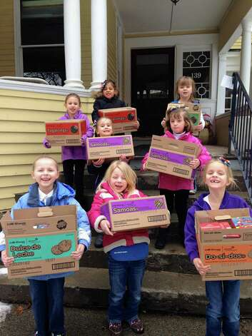 """Members of the kindergarten-aged Daisy's Girl Scout Troop in Clifton Park worked on their """"Make the World a Better Place"""" patch by taking asking people to donate cookies to Albany?s Ronald McDonald House. They delivered 108 boxes on Saturday, March 15. (Photo by Laurel Leal)"""