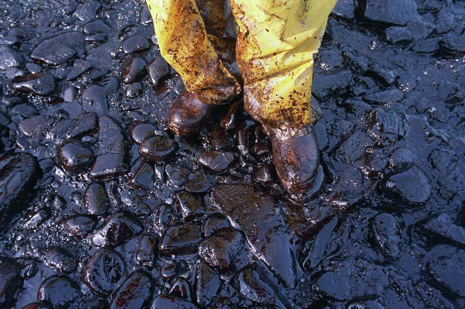 Thick crude oil washed up on the cobble beach of Evans Island sticks to the boots and pants of a local fisherman in Prince William Sound, Alaska, on April 11, 1989.  The Exxon Valdez tanker oil spill on March 24 has blackened hundreds of miles of coastline. Photo: JOHN GAPS III, ASSOCIATED PRESS / AP1989