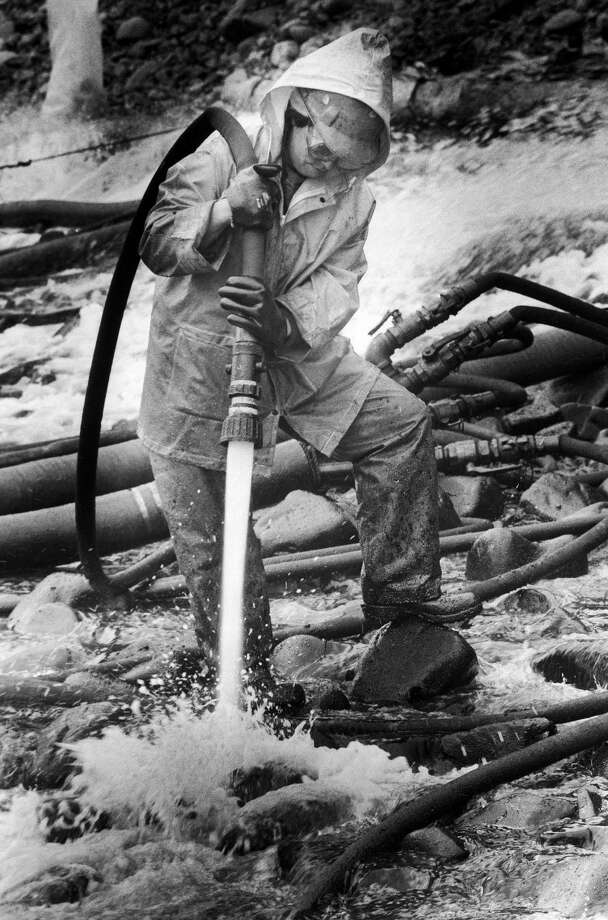 Marcie Thompson uses high pressure hot water to clean oil from the remaining stretch of beach at Point Helen on the south end of Knight Island in Prince William Sound, Alaska, Tuesday, Sept. 12, 1989. Photo: Al Grillo, AP / AP