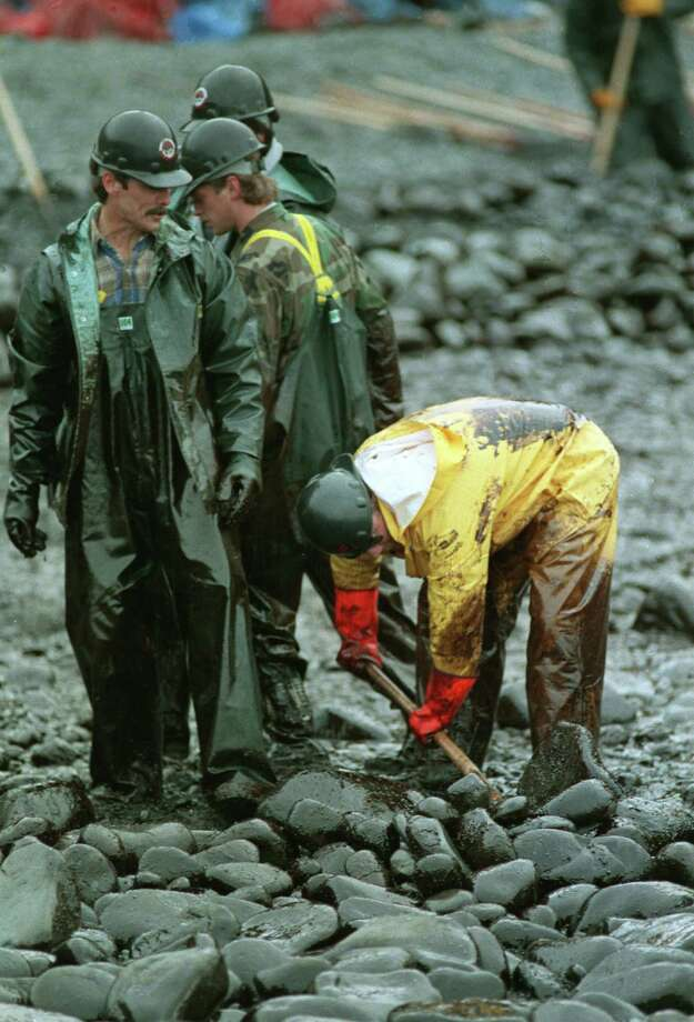 Workmen, covered in oil, shovel oil-covered rocks from the waters edge on Smith Island in Prince William Sound, Alaska, Thursday, March 31, 1989.  An Exxon Valdez crude oil tanker ran aground about 50 miles from Smith Island on March 24. Photo: JACK SMITH, ASSOCIATED PRESS / AP1989