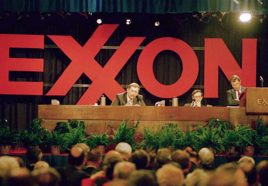 Exxon Corp president Lee Raymond, left, addresses the company's shareholders during their annual meeting, Thursday, May 18, 1989, Parsippany, New Jersey. Company chairman Lawrence Rawl is at right. About 250 demonstrators gathered outside the suburban hotel where the meeting was held, about 35 miles west of New York City. Man in center is unidentified. Photo: Mike Derer, ASSOCIATED PRESS / AP1989