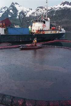 A clean-up worker rakes through crude oil, contained by floating booms off the waters of Prince William Sound, Alaska, April 16, 1989.  The oil, contained here in Snug Harbor off Knight Island, was later sucked off the water by a U.S. Coast Guard skimmer.  Oil from the tanker Exxon Valdez continues to foul the waters of southern Alaska. Photo: JOHN GAPS III, ASSOCIATED PRESS / AP1989