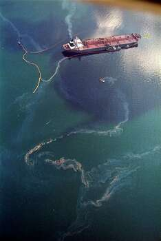 FILE - In this April 9, 1989 file photo, crude oil from the tanker Exxon Valdez, top, swirls on the surface of Alaska's Prince William Sound near Naked Island. The 987-foot tanker, carrying 53 million gallons of crude, struck Bligh Reef at 12:04 a.m. on March 24, 1989, and within hours unleashed an estimated 10.8 million gallons of thick, toxic crude oil into the water. Storms and currents then smeared it over 1,300 miles of shoreline. Twenty five years later, the region, its people and its wildfire are still recovering. Photo: John Gaps III, AP / AP