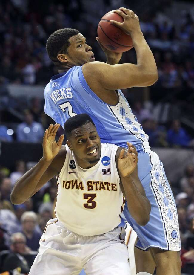 Cyclone defender Melvin Ejim gets crunched under the pivot move of Kennedy Meeks as North Carolina plays Iowa State in the third round of the 2014 NCAA Divison I  Men's Basketball Championship tournament  at the AT&T Center on March 23, 2014.