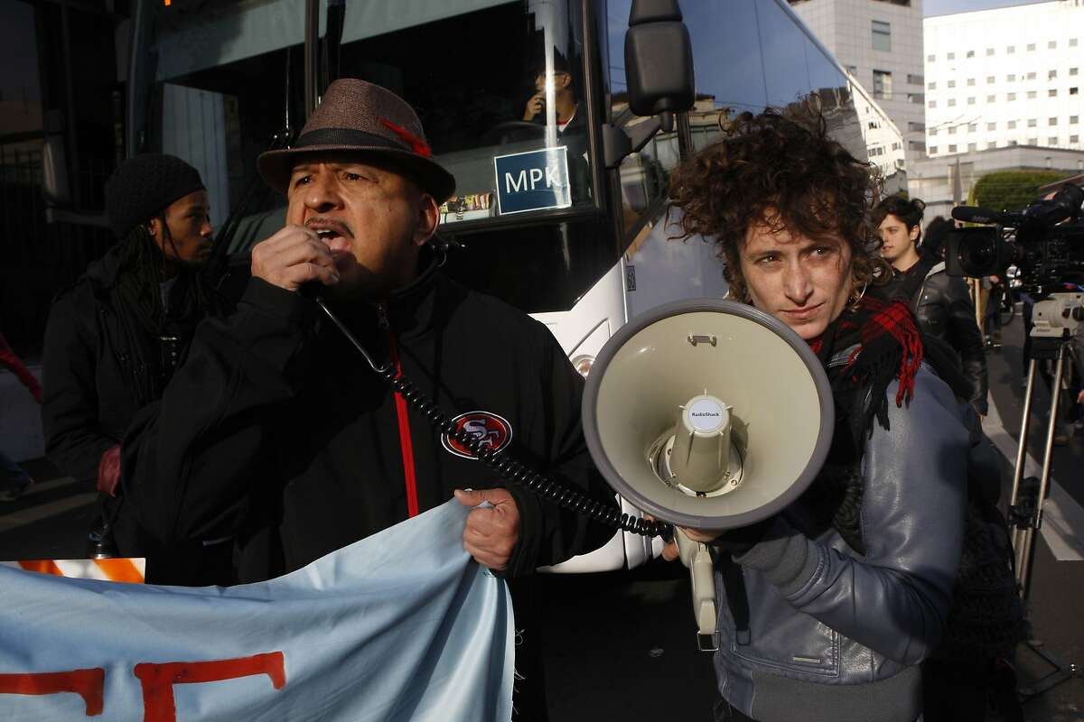 Activists Roberto Hernandez (left) and Erin McElroy (right) block a Facebook bus heading to Menlo Park on 8th at Market streets in San Francisco, Calif., on Tuesday, January 22, 2014.