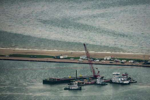 Emergency crews work along a barge that spilled oil after it was struck by a ship near the Texas City Dike on Sunday, March 23, 2014, in Texas City. Dozens of ships are in evolved in clean-up efforts to remove up to 168,000 gallons of oil that make have spilled into Galveston Bay after a ship and barge collided near the Texas City dike on Saturday afternoon. Photo: Smiley N. Pool, Houston Chronicle / © 2014  Houston Chronicle