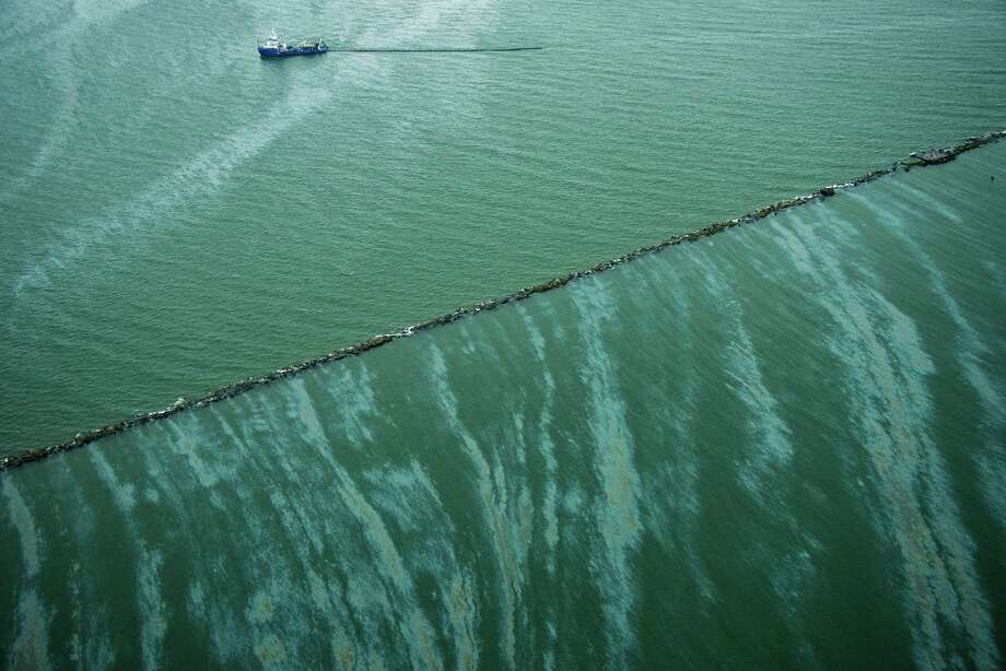 A sheen is seen on the water as a vessel works near the Galveston Jetties on Sunday, March 23, 2014, in Galveston, Texas. Dozens of ships are in evolved in clean-up efforts to remove oil that spilled into Galveston Bay after a ship and barge collided near the Texas City dike on Saturday afternoon. Photo: Smiley N. Pool, Houston Chronicle / © 2014  Houston Chronicle