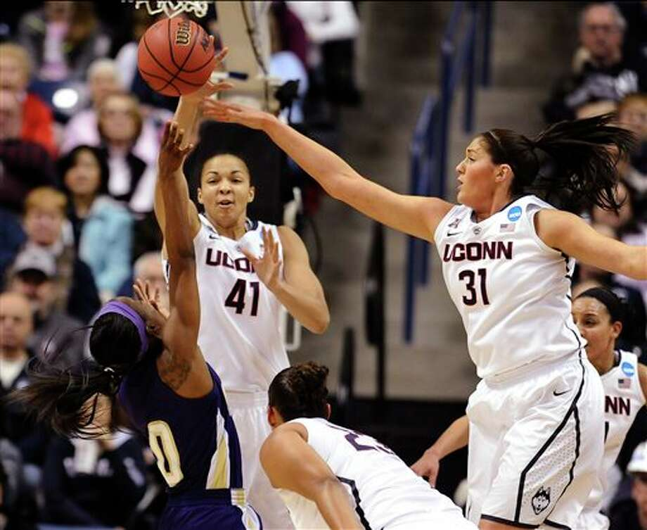 Connecticut's Kiah Stokes  (41) blocks a shot attempt by Prairie View A&M's LaReahn Washington  (0), as Connecticut's Kaleena Mosqueda-Lewis and Stefanie Dolson (31)  defend, during the first half of a first-round game of the NCAA women's  college basketball tournament, Sunday, March 23, 2014, in Storrs, Conn.  (AP Photo/Jessica Hill)