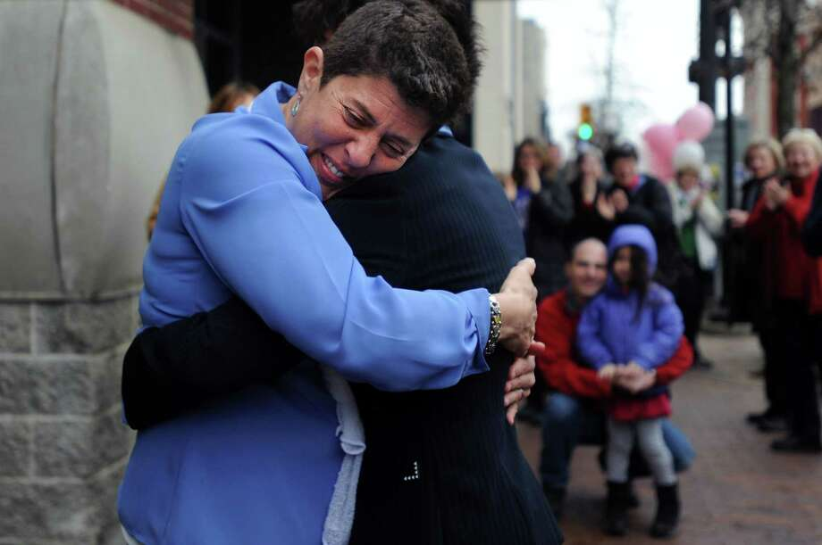 Lisa Ruby hugs Lisa Cavico after they were married after 8 years together outside the Washtenaw County Clerk's office in Ann Arbor, Mich., Saturday, March 22, 2014, the day after a federal court struck down Michigan's ban on gay marriage. (AP Photo/The Ann Arbor News, Brianne Bowen) Photo: Brianne Bowen, MBI / The Ann Arbor News