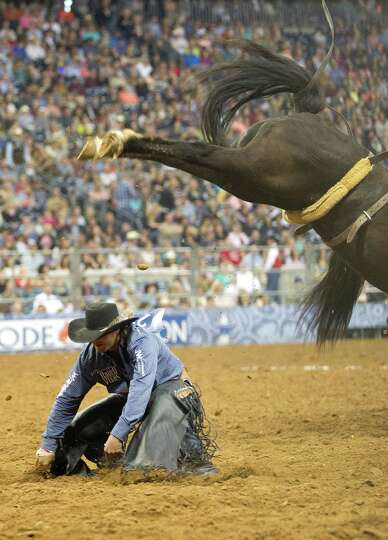 Wade Sundell ducks after jumping off his horse where he received $25,000 for winning the RodeoHousto