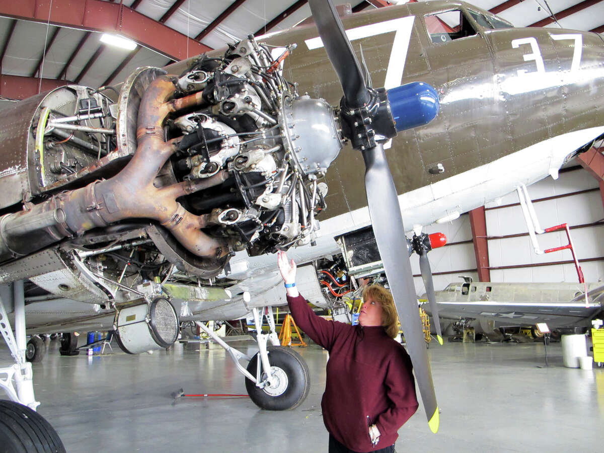 This photo taken March 6, 2014, shows pilot Naomi Wadsworth with a World War II-era Douglas C-47, housed at the National Warplane Museum in Geneseo, N.Y. At the invitation of the French government, the airplane will return to France in June to participate in celebrations marking the 70th anniversary of the D-Day invasion of Normandy. The airplane, known as Whiskey 7 because of its markings, is one of the original troop carriers that dropped paratroopers in advance of the amphibious invasion. In June it will recreate its role and drop paratroopers over the original drop zone in Sainte-Mere-Eglise. (AP Photo/Carolyn Thompson) ORG XMIT: RPCT201