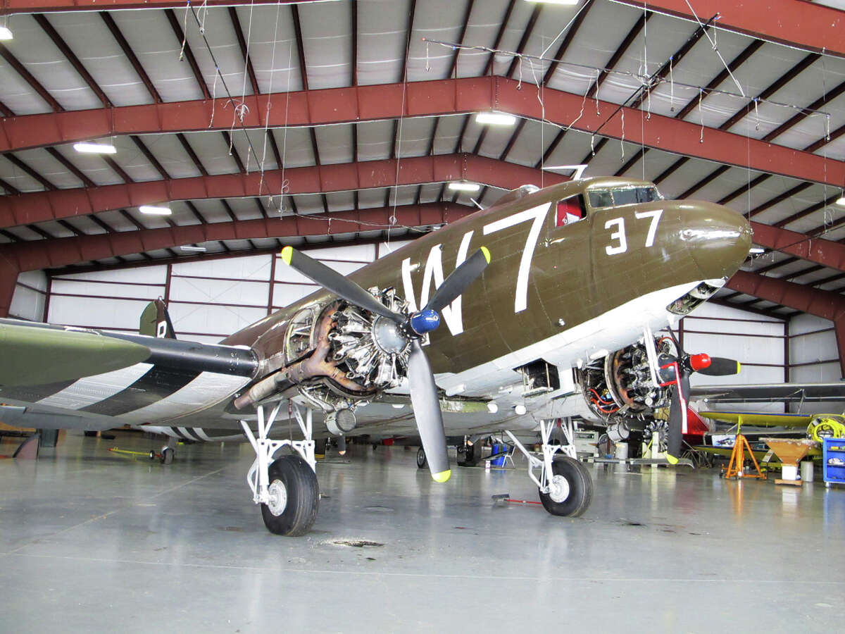 This photo taken March 6, 2014, shows a World War II-era Douglas C-47, housed at the National Warplane Museum in Geneseo, N.Y. At the invitation of the French government, the airplane will return to France in June to participate in celebrations marking the 70th anniversary of the D-Day invasion of Normandy. The airplane, known as Whiskey 7 because of its markings, is one of the original troop carriers that dropped paratroopers in advance of the amphibious invasion. In June it will recreate its role and drop paratroopers over the original drop zone in Sainte-Mere-Eglise. (AP Photo/Carolyn Thompson) ORG XMIT: RPCT202