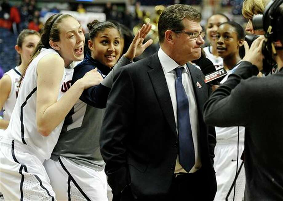 Connecticut's Breanna  Stewart, left, and Kaleena Mosqueda-Lewis, center, sing Happy Birthday  behind head coach Geno Auriemma, right, as he is interviewed on live  television after their 87-44 win over Prairie View A&M in a  first-round game of the NCAA women's college basketball tournament,  Sunday, March 23, 2014, in Storrs, Conn. Today is Auriemma's 60th  birthday. (AP Photo/Jessica Hill)