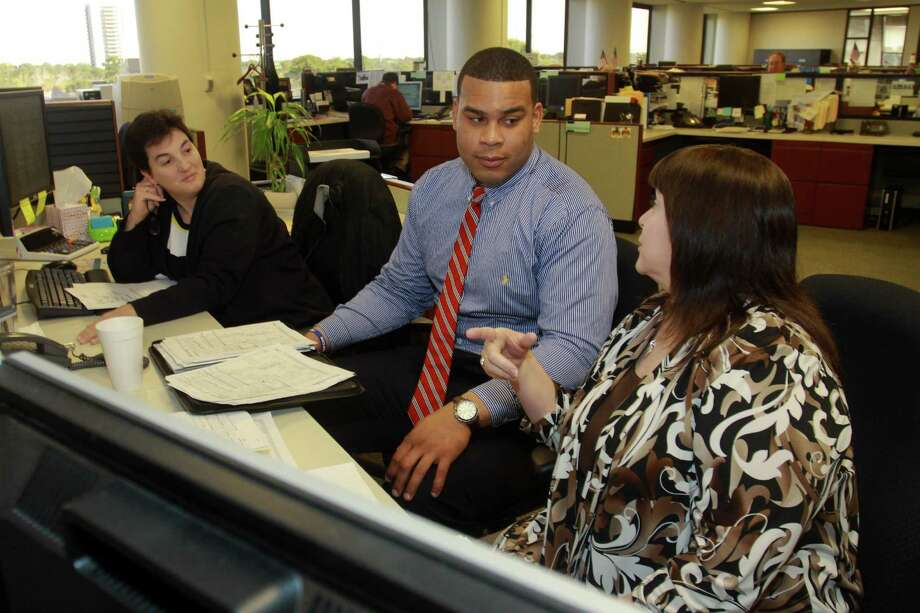 Texans offensive lineman Brandon Brooks works as an intern at Amegy Bank with Dawn Fontana, left, and Kathy Phillips. Photo: Gary Fountain, Freelance / Copyright 2014 by Gary Fountain