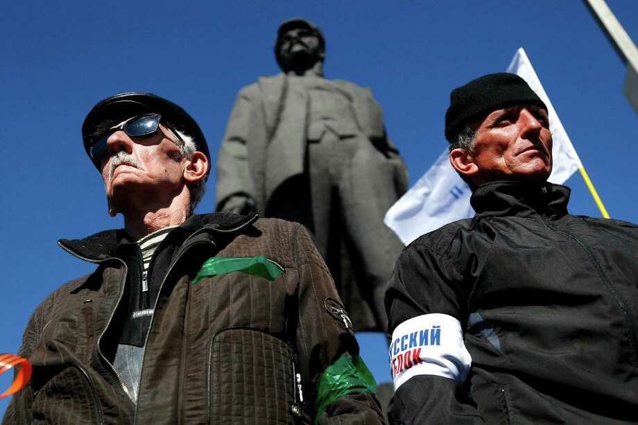 With a statue of Lenin in the background, activists stand guard at a pro-Russia event in Donetsk, where thousands rallied in favor of holding a referendum on secession and absorption into Russia similar to Crimea's. Photo: Sergei Grits, STF / AP