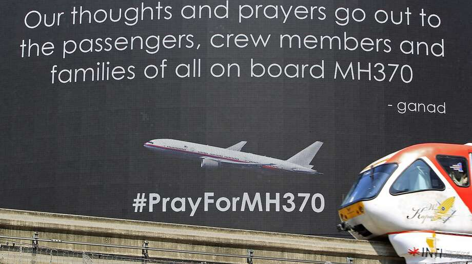 A monorail passenger train passes by a giant electronic screen displaying messages for passengers aboard a missing Malaysia Airlines plane, in Kuala Lumpur, Malaysia, Saturday, March 22, 2014. Six Australian planes took off Saturday for a third day of scouring the desolate southern Indian Ocean for possible parts of missing Malaysia Airlines Flight 370, now lost for two full weeks. (AP Photo/Lai Seng Sin) Photo: Lai Seng Sin, Associated Press
