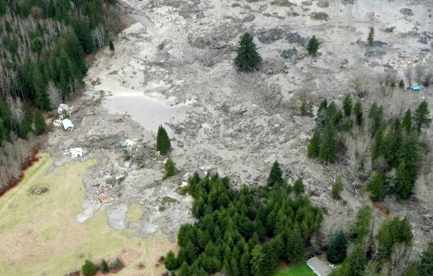 The scene of a massive landslide is shown after it destroyed homes, killed at least three people and created a dam on the North Fork of the Stillaguamash River.