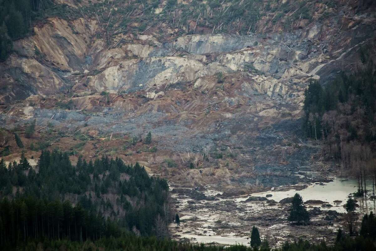 An aerial view shows a huge volume of earth missing from the side of a hill facing Stillaguamish River, in a landslide along State Route 530, between the cities of Arlington and Darrington, on Saturday, March 22, 2014. Search and rescue operations are underway for survivors.
