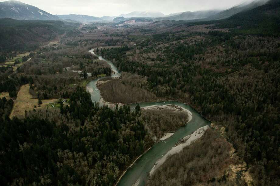 An aerial view of the Stillaguamish River leading up to the landslide, above, that shows a huge volume of earth missing from the side of a hill, along State Route 530 between the cities of Arlington and Darrington, on Saturday, March 22, 2014. Photo: Marcus Yam/The Seattle Times/via AP / The Seattle Times