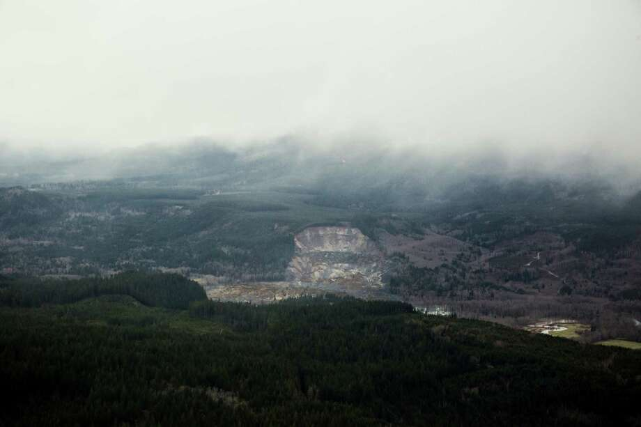 A wide aerial view shows a huge volume of earth missing from the side of a hill facing the Stillaguamish River, in a landslide along State Route 530, between the cities of Arlington and Darrington, on Saturday, March 22, 2014. Search and rescue operations are underway for survivors. Photo: Marcus Yam/The Seattle Times/via AP / The Seattle Times