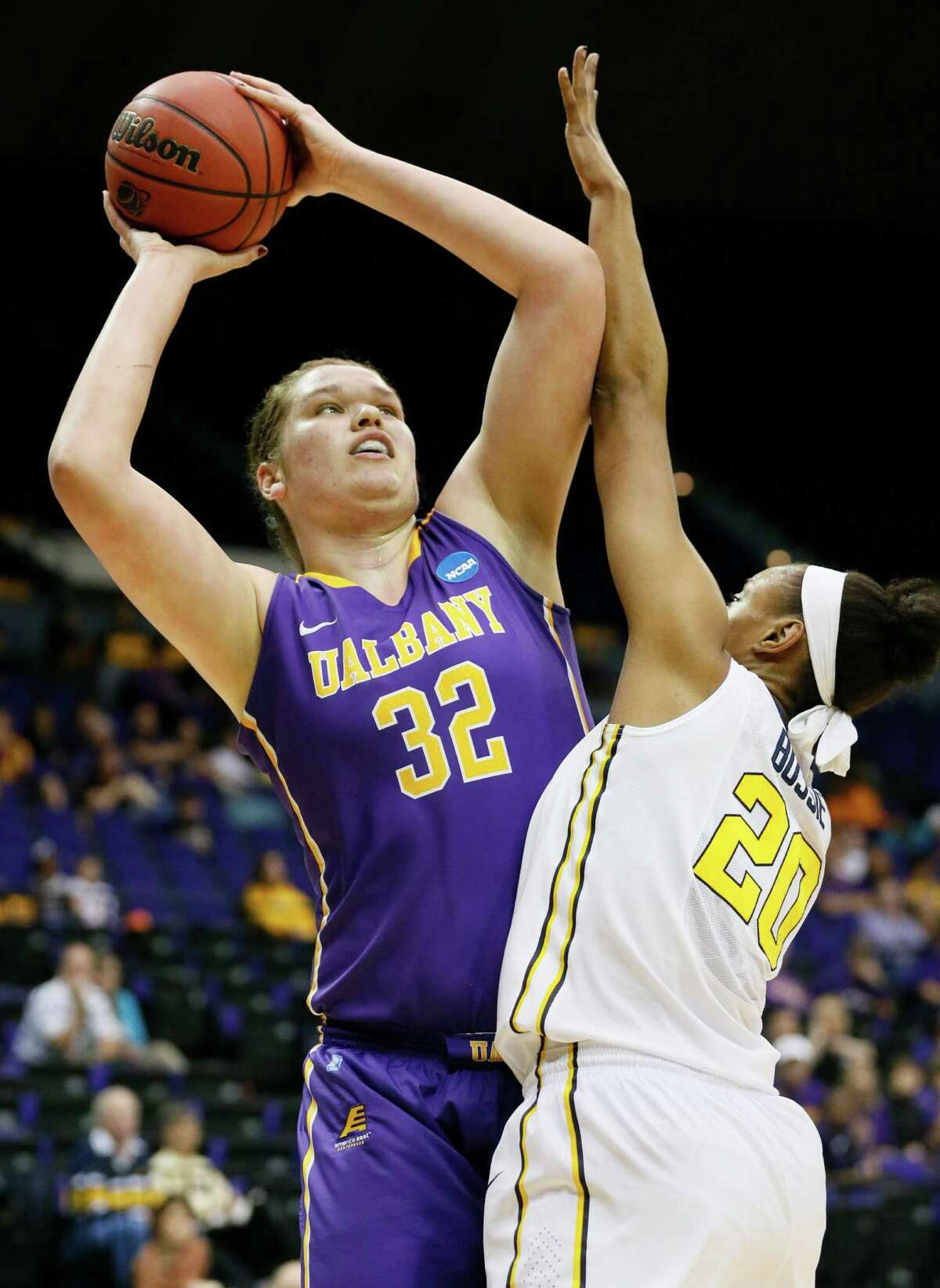 Albany center Megan Craig (32) attempts a shot at the basket while West Virginia center Asya Bussie (20) defends in the first half of an NCAA college basketball first-round tournament game on Sunday, March 23, 2014, in Baton Rouge, La. (AP Photo/Rogelio V. Solis) ORG XMIT: LARS114