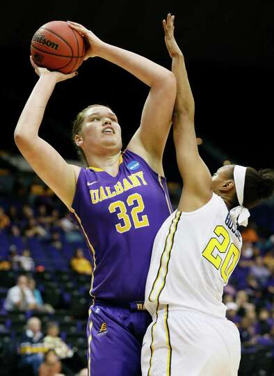 Albany center Megan Craig (32) attempts a shot at the basket while West Virginia center Asya Bussie