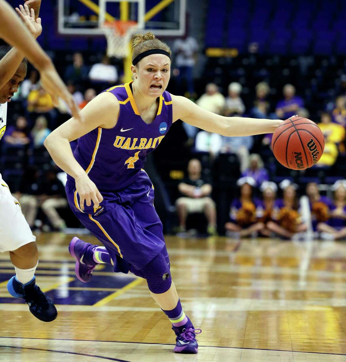 Albany guard Sarah Royals (4) dribbles around West Virginia defenders in the first half of an NCAA college basketball first-round tournament game on Sunday, March 23, 2014, in Baton Rouge, La. (AP Photo/Rogelio V. Solis) ORG XMIT: LARS115