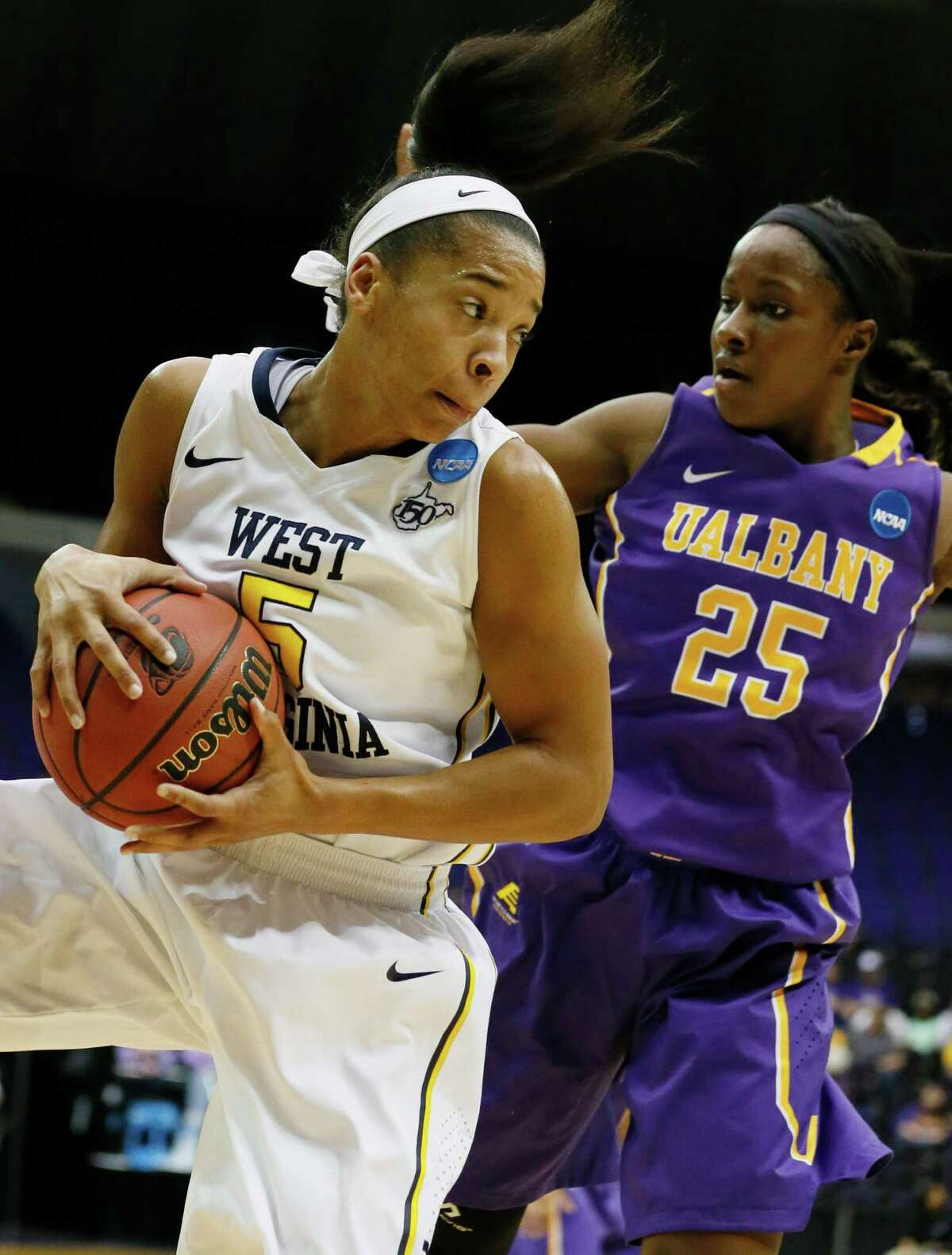 West Virginia forward Averee Fields (5) looks for an open teammate after pulling down a rebound past the defense of Albany forward Shereesha Richards (25) in the first half of an NCAA college basketball first-round tournament game on Sunday, March 23, 2014, in Baton Rouge, La. (AP Photo/Rogelio V. Solis) ORG XMIT: LARS116