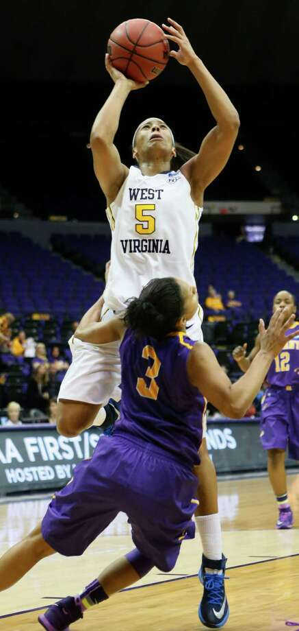 West Virginia's Averee Fields, top, shoots over Albany's Margarita Rosario in the second half of an NCAA college basketball first-round tournament game on Sunday, March 23, 2014, in Baton Rouge, La. (AP Photo/Rogelio V. Solis) ORG XMIT: LARS12 Photo: Rogelio V. Solis / AP