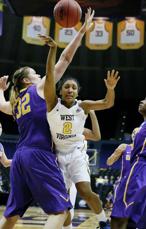 West Virginia guard Taylor Palmer (2) goes airborne after being fouled by Albany center Megan Craig (32) in the second half of an NCAA college basketball first-round tournament game on Sunday, March 23, 2014, in Baton Rouge, La. West Virginia won 76-61. (AP Photo/Rogelio V. Solis) ORG XMIT: LARS123 Photo: Rogelio V. Solis / AP