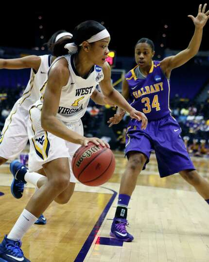 West Virginia guard Christal Caldwell (1) dribbles past Albany guard Cassandra Edwards (34) in the f