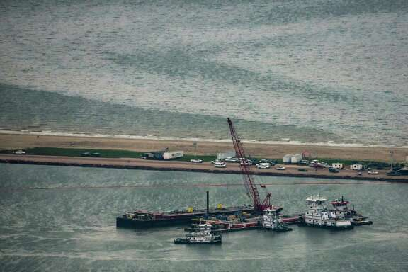 Emergency crews work along a barge that spilled oil after it was struck by a ship near the Texas City Dike on Sunday. Dozens of ships are in involved in clean-up efforts.