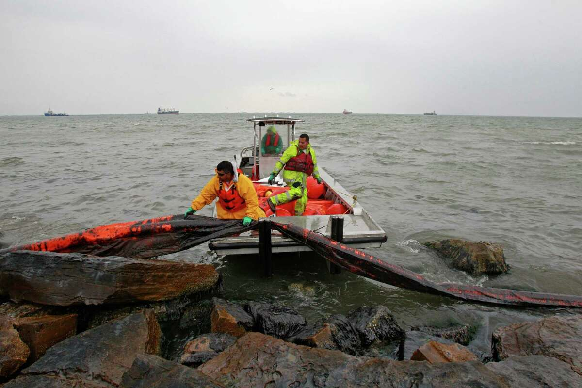 Workers try to move an oil containment boom on the eastern end of Galveston Bay on March 23. Nearly a month after the spill, cleanup efforts are nearly complete.
