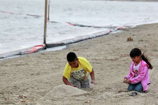 Ramero Torres, 9, and his sister, Yosselyn Donjuan, 6, of Pasadena play near an oil containment boom that washed to the shore on the beach area along Boddeker Rd. on the Eastern end of Galveston near the ship channel Sunday, March 23, 2014 in Galveston. Photo: Melissa Phillip, Houston Chronicle / © 2014  Houston Chronicle