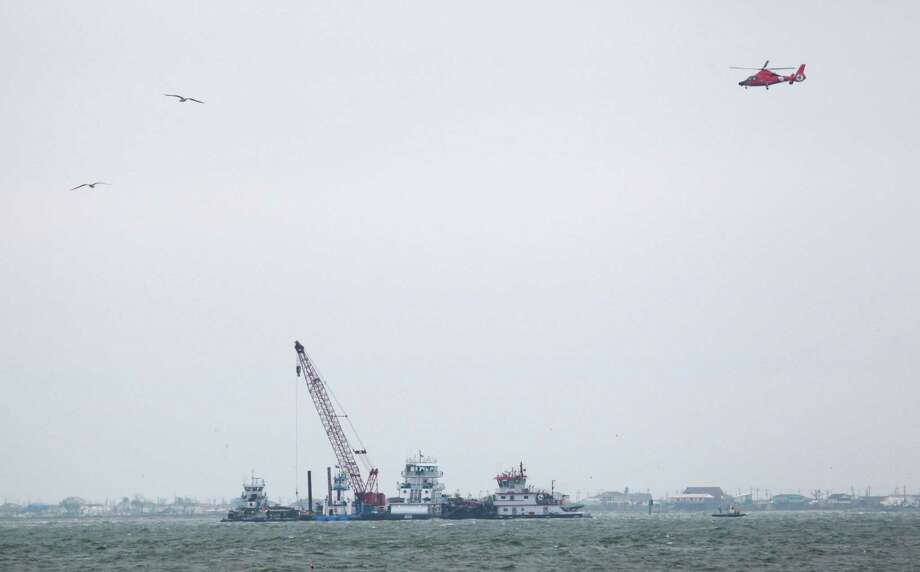 A Coast Guard helicopter flies over as emergency crews work along a barge that spilled oil after it was struck by a ship near the Texas City Dike Sunday, March 23, 2014 in Texas City. Photo: Melissa Phillip, Houston Chronicle / © 2014  Houston Chronicle