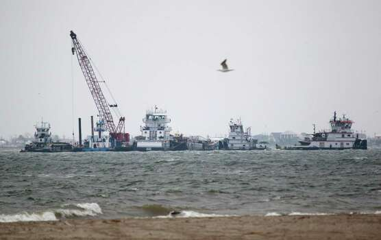Emergency crews work along a barge that spilled oil after it was struck by a ship near the Texas City Dike Sunday, March 23, 2014 in Texas City. Photo: Melissa Phillip, Houston Chronicle / © 2014  Houston Chronicle