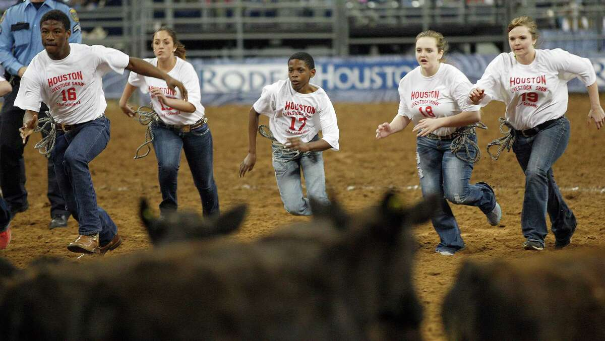 Children run during RodeoHouston's calf scramble competition on the last day of the event Sunday at Reliant Stadium.