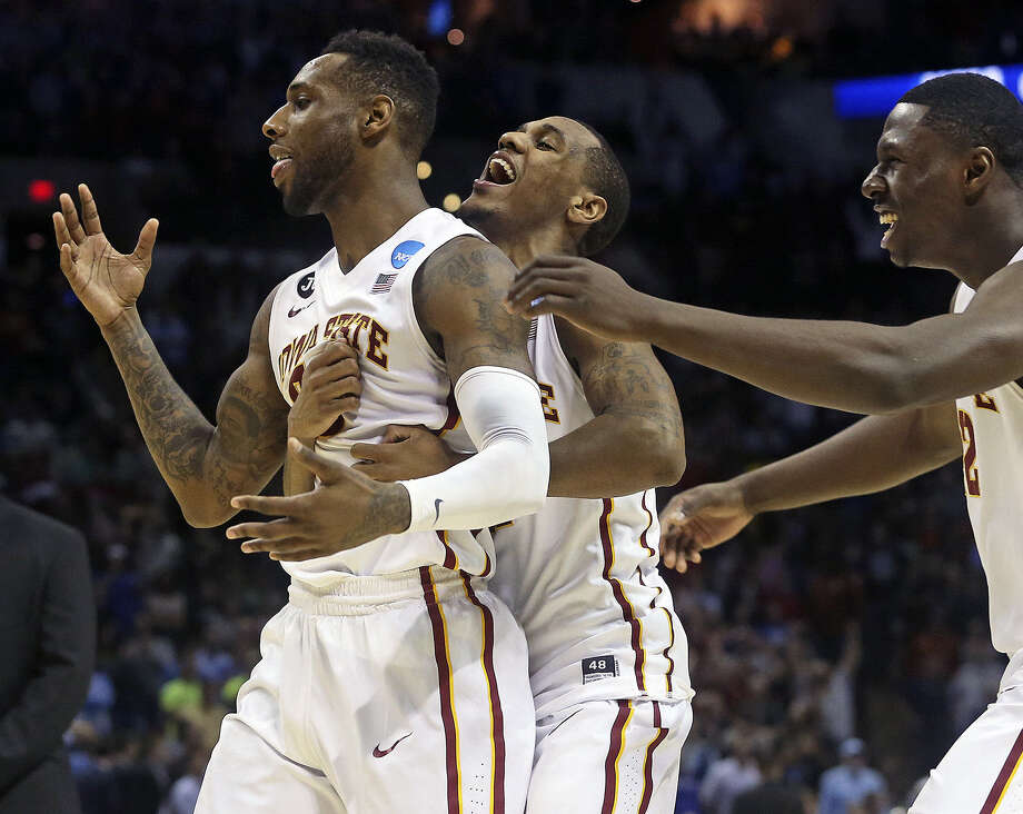 DeAndre Kane (from left) is mobbed by teammates Monte Morris and Daniel Edozie after his basket beat North Carolina 85-83. Photo: Tom Reel / San Antonio Express-News