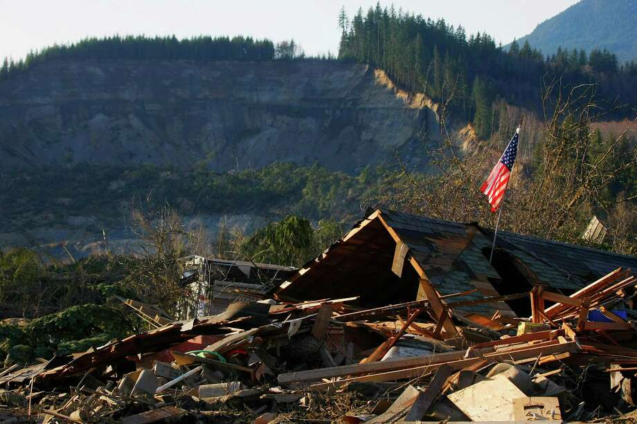 A flag sits atop what was Cory Kuntz and family's home Sunday,  March 23, 2014. The family was at a baseball game Saturday morning when the fatal mudslide swept through the area, destroying everything on their property. The area where the land broke away is seen in the background. Photo: GENNA MARTIN, THE EVERETT HERALD