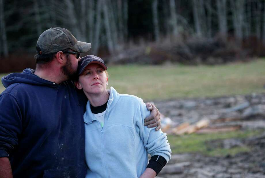 Volunteers Frank and Rhonda Cook watch as the final body they recovered Sunday afternoon is lifted into a helicopter on the east side of Saturday's fatal mudslide near Oso, Wash. The couple started at 6 a.m. searching the area Sunday, March 23, 2014.  Photo: GENNA MARTIN, THE EVERETT HERALD
