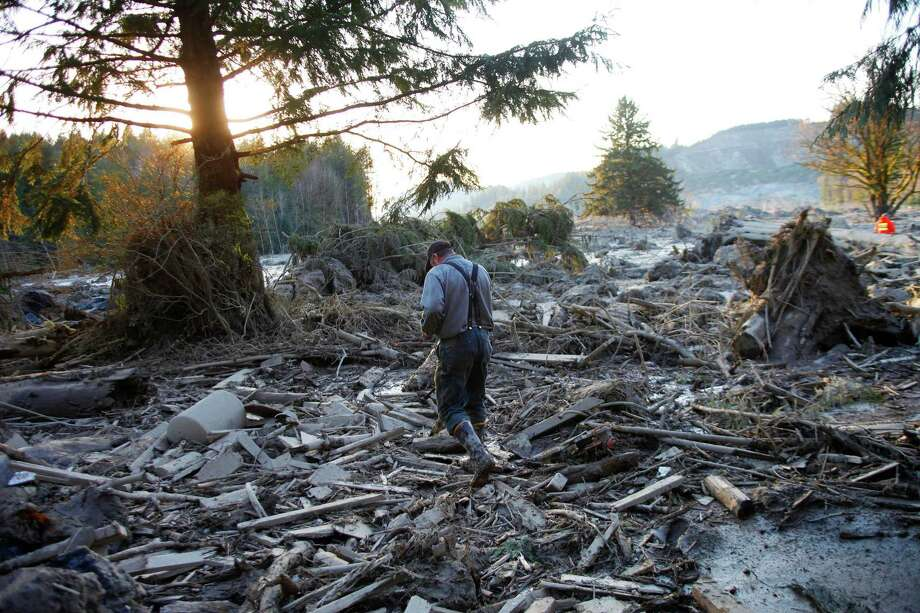 Steve Skaglund walks across the rubble on the east side of Saturday's fatal mudslide near Oso, Wash., Sunday, March 23, 2014.  Photo: GENNA MARTIN, THE EVERETT HERALD