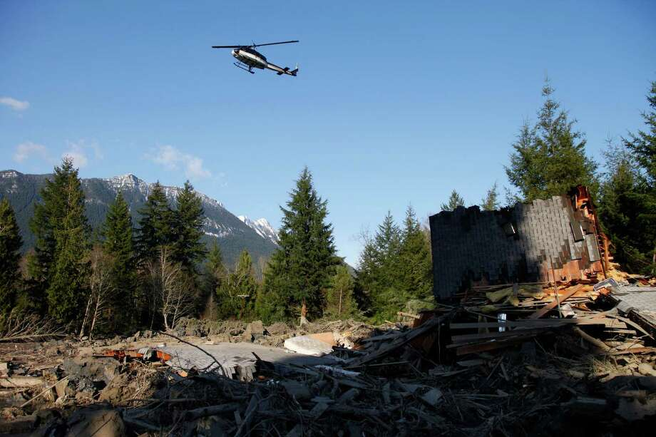 A helicopter flies low over the mudslide effected area Sunday, March 23, 2014, in Oso, Wash. Photo: GENNA MARTIN, THE EVERETT HERALD