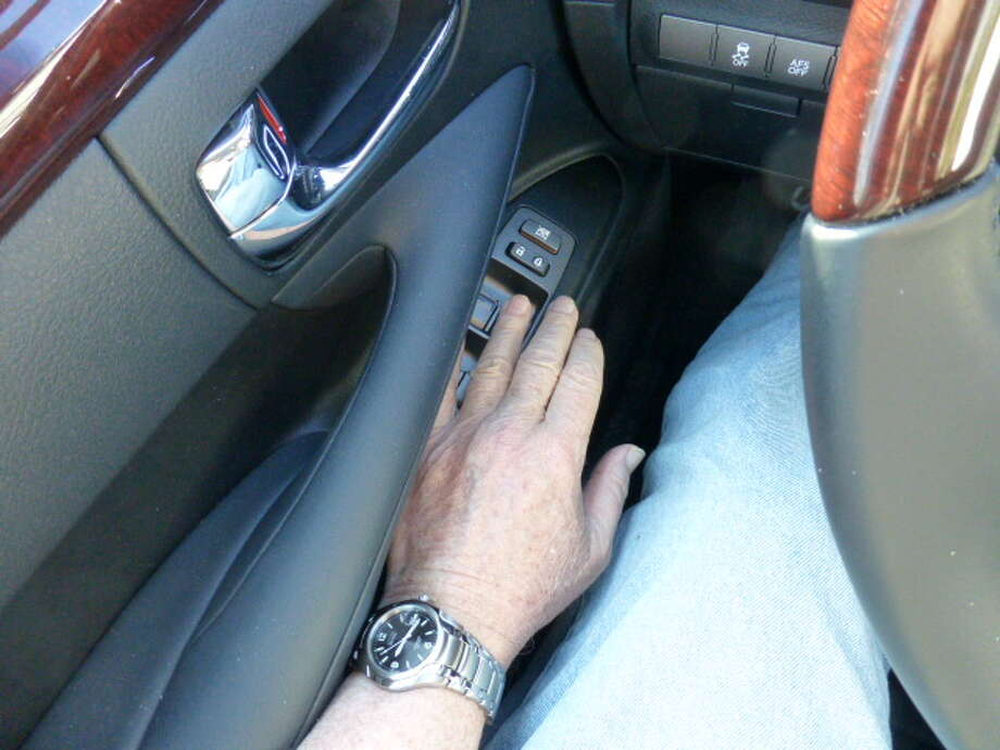 Hand straight out. Toyota/Lexus could have designed the door in a way that the window buttons fall readily to hand.