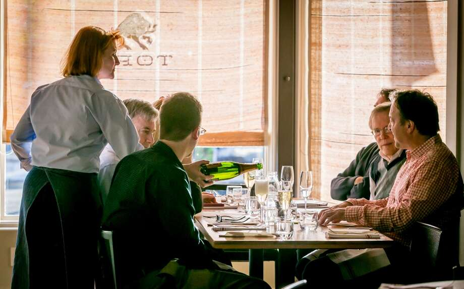 A server pours Champagne for a table at Torc in Napa. Photo: John Storey, Special To The Chronicle