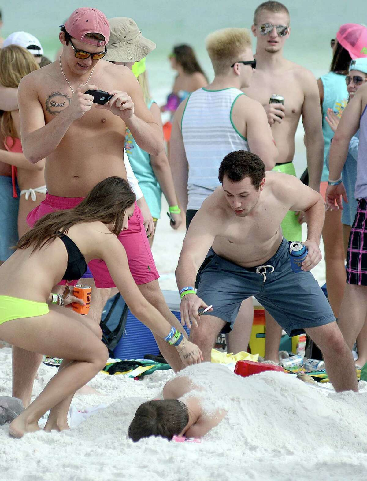 Spring breakers photograph their friend sleeping on the beach on Tuesday, March 18, 2014 in Destin, Fla.