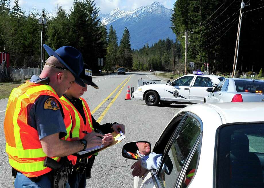 State troopers work at a roadblock near the landslid on Sunday. Photo: By Weldon Wilson