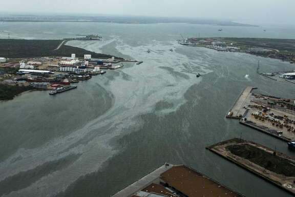 Cleanup vessels are surrounded by a sheen on the water in the Port of Galveston on Sunday, March 23, 2014, in Galveston, Texas. Dozens of ships are in evolved in clean-up efforts to remove oil that spilled into Galveston Bay after a ship and barge collided near the Texas City dike on Saturday afternoon.