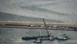 Emergency crews work along a barge that spilled oil after it was struck by a ship near the Texas City Dike on Sunday, March 23, 2014, in Texas City. Dozens of ships are in evolved in clean-up efforts to remove up to 168,000 gallons of oil that make have spilled into Galveston Bay after a ship and barge collided near the Texas City dike on Saturday afternoon.