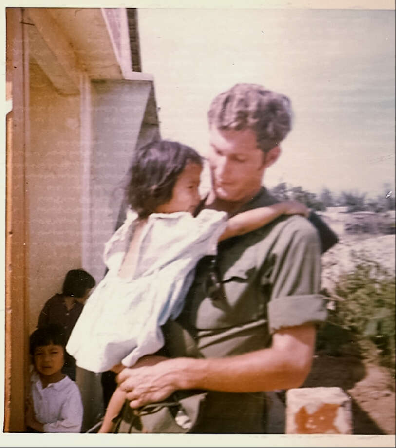 Army Spc. 5 Lew Benton of Saratoga Springs, a medic, holds a Vietnamese youngster during a visit to a village near Chu Lai. (Provided photo)